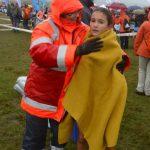Voluntario tapando con una manta a atleta en la meta