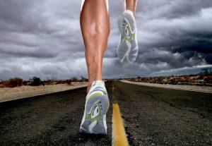 piernas de un atleta corriendo solo en el asfalto